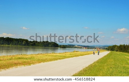 Well known Danube cycle trail running along the Danube river in Austria and two cyclists ride along cycle path during beautiful weather in the summer. - stock photo