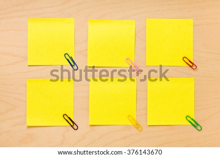 well-ordered yellow blank postit notes with colored clips on a wooden board
