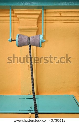 well pulley and his rope on a fresh painted wall in an indian temple, Melaka, Malaysia