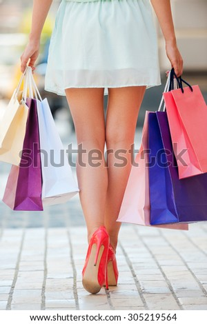Well spent day. Close-up of young woman carrying shopping bags while walking along the street - stock photo