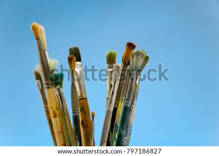 Well used artists paintbrushes on a blue background