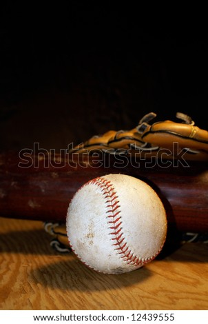Well used baseball, bat and glove rest on a sheet of plywood.