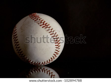 Well used baseball on a black reflective surface - stock photo