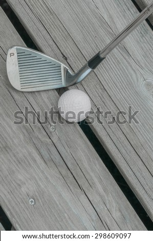 "Well-used golf club pitching wedge (marked ""P"") and golf ball on a weathered wooden deck."