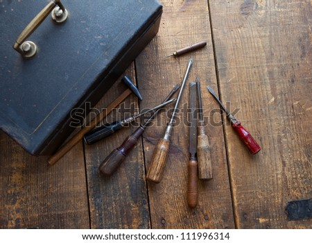 Well used old tools and black tool box on rough wood surface. - stock photo