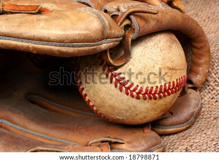 Well worn and used baseball in the pocket of a baseball mitt. - stock photo