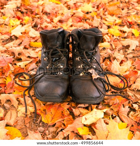 Well worn leather hiking boots on fall colored autumn leaves in forest ready to be taken on a hike
