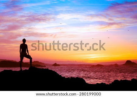 wellbeing concept, silhouette of person enjoying beautiful sunset with view of ocean  - stock photo