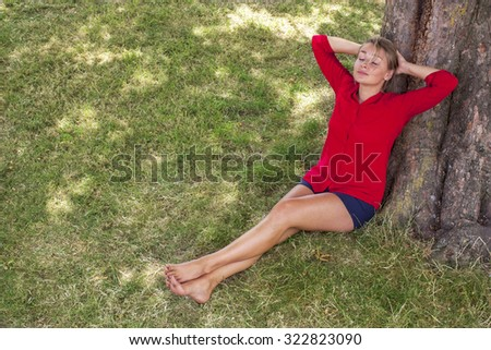 wellbeing & tree concept - cheerful young suntanned blond woman lying under a tree,closing eyes enjoying freedom,natural summer daylight,view from above - stock photo