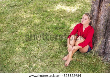 wellbeing & tree concept - smiling young suntanned blond woman sitting under a tree,closing eyes enjoying freshness,natural summer daylight,view from above - stock photo