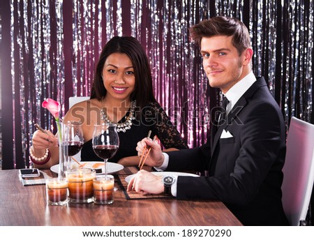 Welldressed young couple having meal at restaurant table