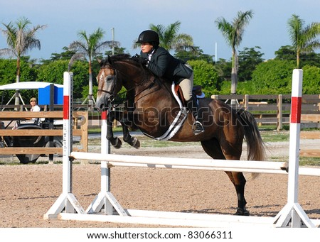 WELLINGTON, FLORIDA - AUGUST 13: An unidentified rider takes a fence at the South Florida Hunter Jumper Association's Summer Series on August 13, 2011 in Wellington, Florida.