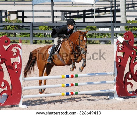 WELLINGTON, FLORIDA -October 10, 2015: Zachary Pierre and Beau Alezan, a chestnut horse, clearing a jump at the ESP Fall I competition held at the Palm Beach International Equestrian Center