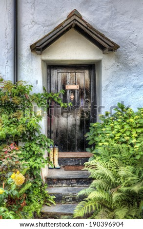 Wellingtons Decorating the Stairs Leading to a Cottage - stock photo