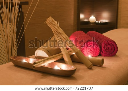 Wellness and spa concept with candles, red towels and part of massage table. - stock photo