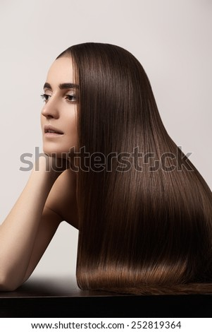 Wellness and spa. Sensual woman model with straight dark hair. Shiny long health hairstyle. Beauty and haircare. Natural look with naturel makeup, strong eyebrows, clean skin - stock photo