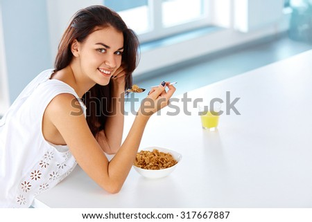 Wellness concept. Beautiful young woman  having breakfast and smiling. Healthy eating