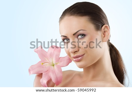 wellness portrait of young woman with pink lily looking in camera with a smile