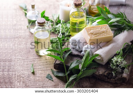 Wellness setting. Essential aroma oil, towels, soap on aged  wooden background. Selective focus.  - stock photo