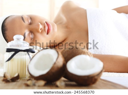 Wellness & spa treatment with coconut oil, feminine relaxation. Figure of a woman in the office of the spa during surgery care.   - stock photo
