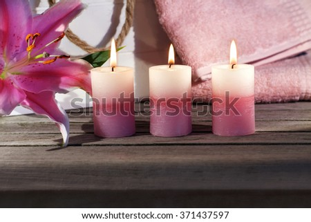 Wellness still life with flower and candles on a wooden table