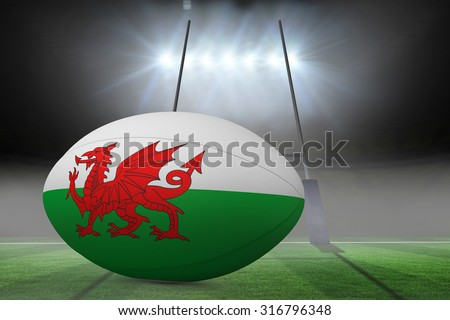 Welsh flag rugby ball against rugby pitch - stock photo