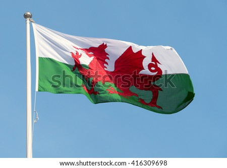 Welsh flag (Y Ddraig Goch) blowing in the wind. - stock photo