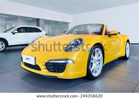 WENZHOU-CHINA-NOV. 19, 2014. Yellow Porsche 911 in showroom. US as Porsche's largest single market might end in 2015, China will replace it, predicts Porsche head sales and marketing Bernhard Maier. - stock photo