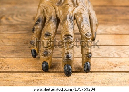 Werewolf hand on rustic wooden table close up  for Halloween - stock photo