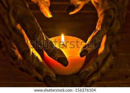 Werewolf hands and candlelight for Halloween concept - stock photo