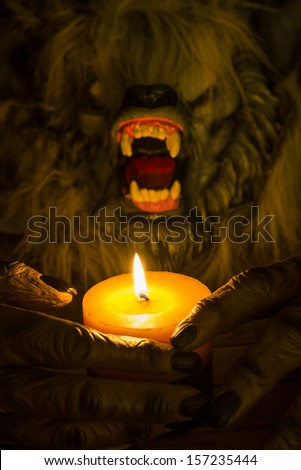 Werewolf head and the hands cradling a candle close up  - stock photo