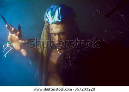 Werewolf with long nails and crooked teeth among the branches of the tree and blue smoke. Gothic image of scary diabolical creatures for Halloween - stock photo