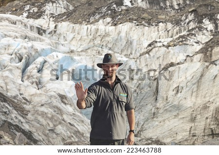 WEST COAST, NEW ZEALAND -MAY 20: Park Ranger in stop action as warning sign at Fox Glacier on May 20, 2013 in West Coast, NZ. Many tourists have died or been seriously injured after ignoring this sign - stock photo