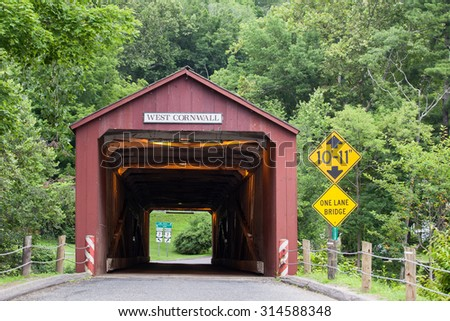 WEST CORNVALL, CONNECTICUT - JULY 15, 2015: The 1864 West Cornwall Covered Bridge. also known as Hart Bridge, is a wooden bridge over the Housatonic River on July 15, 2015 in West Cornwall, CT. - stock photo