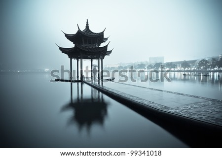 west lake of hangzhou and ancient pavilion at night - stock photo