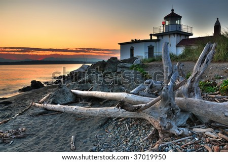 West Point lighthouse at Discovery park Seattle at dusk with drift wood in the foreground - stock photo