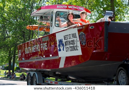 WEST ST. PAUL, MINNESOTA - MAY 21, 2016: Annual West St. Paul Days Grande Parade led by South Metro Fire automobile with water rescue boat traveling up Smith Avenue in West St. Paul on May 21.  - stock photo
