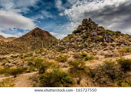 West Texas Landscape of Desert Area with very rocky Hills full of graffiti and a cross on top. - stock photo