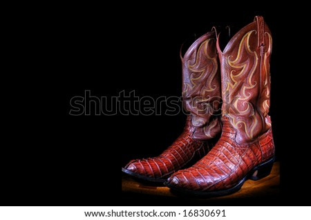 Western cowboy boots on black background - stock photo
