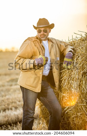 Western cowboy style man with a rope outdoor portrait in sunshine. evening light