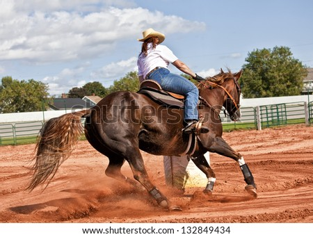 Western horse and rider competing in pole bending and barrel racing competition. - stock photo