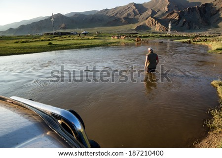 WESTERN MONGOLIA, MONGOLIA - AUG 13, 2012: Foreign tourists in cars crossing small river. - stock photo