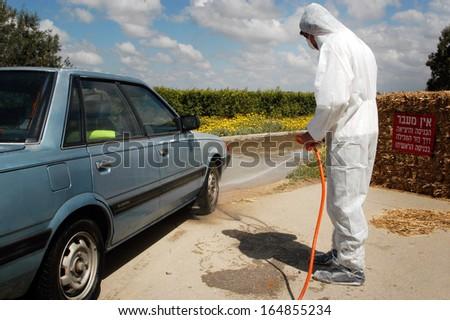 WESTERN NEGEV, ISRAEL - MARCH 18: Agriculture Ministry worker wash a vehicle during bird Flu outbreak in a forklift at Kibbutz Holit in the western Negev, Israel on March 19, 2006. - stock photo