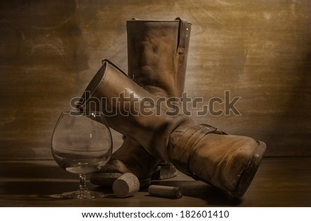western still life with old cowboy boots, cartridge and brandy on wooden background