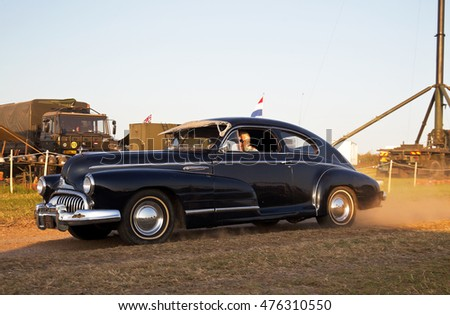 WESTERNHANGER, UK - JULY 20: A vintage Buick motorcar heads out onto the arena road after the public have left the show for the day at the War & Peace Revival show on July 20, 2016 in Westernhanger