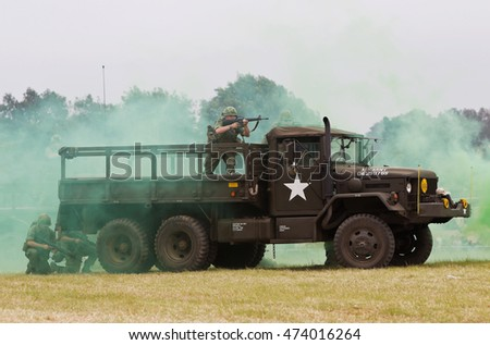 WESTERNHANGER, UK - JULY 20: An ex US army gun lorry enters the main arena with all guns blazing as part of a Vietnam war re-enaction at the W&P show on July 20, 2016 in Westernhanger