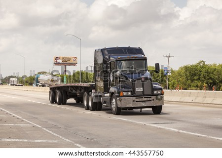 WESTLAKE, USA - APR 15, 2016: Black Kenworth T-660 semitrailer truck with a flatbed trailer on the highway. Louisiana, United States