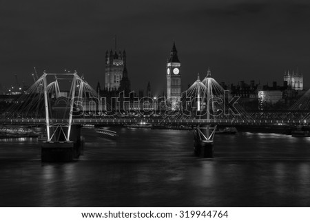 Westminster at Night from across the River Thames in black and white. Part of Jubilee/Hungerford Bridge can be seen in the foreground. - stock photo