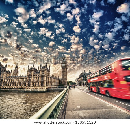 Westminster Bridge traffic at sunset. Blurred Red Bus crossing the street. - stock photo