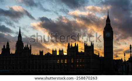 Westminster palace and Big Ben in London at sunset. Backlight technique, clouds in the sky and reflections on the river surface